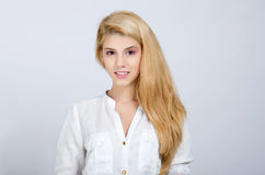 Muchacha rubia joven hermosa en la sonrisa blanca de la camisa. Fotografía de archivo