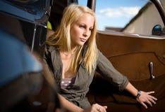 Muchacha rubia joven hermosa en un coche negro de la vendimia. Fotografía de archivo libre de regalías