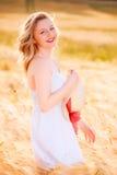 Muchacha rubia joven hermosa feliz en el vestido blanco con el sombrero de paja Fotos de archivo libres de regalías