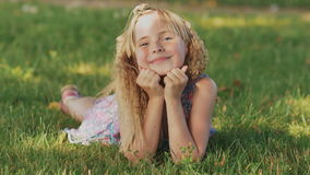 Muchacha rubia joven hermosa que miente en un campo, hierba verde Al aire libre disfrute de la naturaleza Muchacha sonriente sana almacen de metraje de vídeo