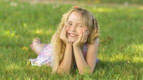 Muchacha rubia joven hermosa que miente en un campo, hierba verde Al aire libre disfrute de la naturaleza Muchacha sonriente sana Fotografía de archivo