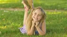 Muchacha rubia joven hermosa que miente en un campo, hierba verde Al aire libre disfrute de la naturaleza Muchacha sonriente sana Fotos de archivo