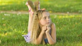 Muchacha rubia joven hermosa que miente en un campo, hierba verde Al aire libre disfrute de la naturaleza Muchacha sonriente sana Foto de archivo libre de regalías