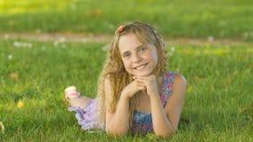 Muchacha rubia joven hermosa que miente en un campo, hierba verde Al aire libre disfrute de la naturaleza Muchacha sonriente sana Fotos de archivo libres de regalías