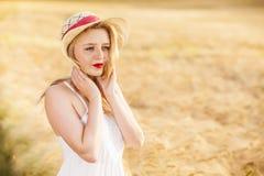 Muchacha rubia joven hermosa sola en el vestido blanco con el sombrero de paja Imagen de archivo