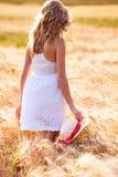 Muchacha rubia joven hermosa sola en el vestido blanco con el sombrero de paja Imagenes de archivo