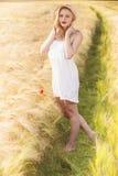 Muchacha rubia joven hermosa sola en el vestido blanco con el sombrero de paja Imagen de archivo libre de regalías