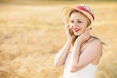 Muchacha rubia joven hermosa sola en el vestido blanco con el sombrero de paja Fotografía de archivo