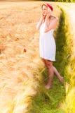 Muchacha rubia joven hermosa sola en el vestido blanco con el sombrero de paja Fotos de archivo