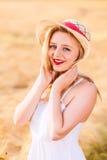 Muchacha rubia joven hermosa sola en el vestido blanco con el sombrero de paja Foto de archivo
