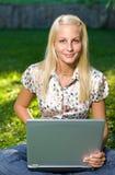 Muchacha rubia joven linda con la computadora portátil al aire libre Imágenes de archivo libres de regalías