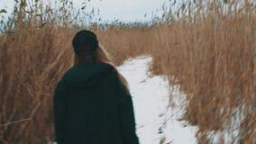 Muchacha rubia joven que camina en la trayectoria de la nieve entre juncia teñida en día nublado del invierno metrajes