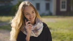 Muchacha rubia joven que habla por el teléfono almacen de video