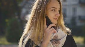Muchacha rubia joven que habla por el teléfono metrajes
