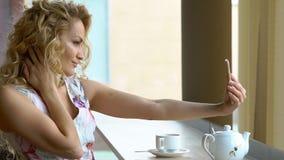 Muchacha rubia joven que hace el autorretrato en su teléfono elegante almacen de video