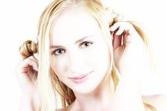 Muchacha rubia joven que juega con su pelo Imagenes de archivo