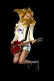 Muchacha rubia joven que salta con la guitarra eléctrica Fotos de archivo
