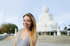 Muchacha rubia joven que se coloca con la estatua de Buda en Phuket, Tailandia Fotos de archivo