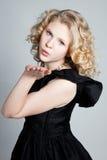 Muchacha rubia joven que sopla un beso Foto de archivo libre de regalías