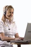 Muchacha rubia joven que trabaja en la computadora portátil con el receptor de cabeza Imágenes de archivo libres de regalías