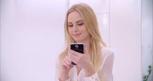 Muchacha rubia joven que usa el teléfono móvil almacen de video
