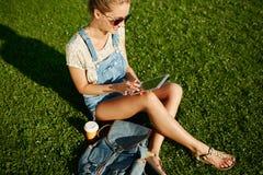 Muchacha rubia joven que usa la sentada al aire libre de la tableta en hierba imágenes de archivo libres de regalías