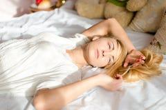 Muchacha rubia joven sincera atractiva relajante de la oferta de la mujer que miente en cama en la luz del sol imágenes de archivo libres de regalías