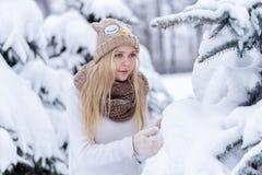 Muchacha rubia joven sonriente atractiva que camina en mujer bonita del bosque del invierno en el invierno al aire libre Ropa del Imagen de archivo libre de regalías