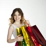 Muchacha rubia joven sonriente con los panieres coloridos en d blanca Imagen de archivo libre de regalías