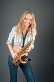 Muchacha rubia joven sonriente feliz con el saxofón Fotografía de archivo libre de regalías