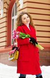 Muchacha rubia joven y elegante hermosa en la capa roja que sostiene las flores Accesorios para mujer Primavera Fotos de archivo