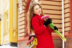 Muchacha rubia joven y elegante hermosa en la capa roja que sostiene las flores Accesorios para mujer Primavera Fotografía de archivo libre de regalías