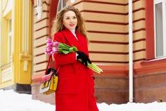 Muchacha rubia joven y elegante hermosa en la capa roja que sostiene las flores Accesorios para mujer Primavera Fotos de archivo libres de regalías