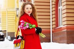 Muchacha rubia joven y elegante hermosa en la capa roja que sostiene las flores Accesorios para mujer Primavera Imágenes de archivo libres de regalías