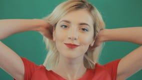 Muchacha rubia juguetona feliz con el pelo largo y los labios rojos sensuales que presentan en fondo verde Retrato de la mujer jo almacen de metraje de vídeo