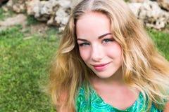 Muchacha rubia linda del adolescente en un parque en un día de verano Imágenes de archivo libres de regalías