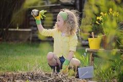 Muchacha rubia linda del niño que se divierte que juega al pequeño jardinero Foto de archivo libre de regalías