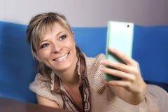 Muchacha rubia linda en el sofá Ella mira su smartphone y hace a fotos de archivo libres de regalías