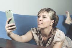 Muchacha rubia linda en el sofá Ella mira su smartphone y hace un selfie foto de archivo