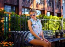 Muchacha rubia linda en gafas de sol y pantalones cortos del dril de algodón Fotos de archivo