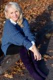 Muchacha rubia linda hermosa en una chaqueta azul que se sienta en el camino en el parque del otoño Fotografía de archivo