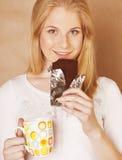 Muchacha rubia linda joven que come el chocolate y Imágenes de archivo libres de regalías