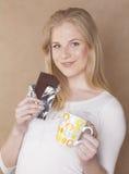 Muchacha rubia linda joven que come el chocolate y Fotografía de archivo