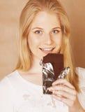 Muchacha rubia linda joven que come el chocolate y Fotografía de archivo libre de regalías