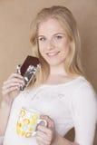 Muchacha rubia linda joven que come el chocolate y Foto de archivo libre de regalías