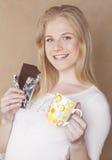 Muchacha rubia linda joven que come el chocolate y Fotos de archivo libres de regalías