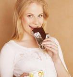 Muchacha rubia linda joven que come el chocolate y Imagen de archivo libre de regalías