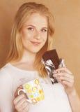 Muchacha rubia linda joven que come el chocolate y que bebe ascendente cercano del café Foto de archivo