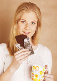 Muchacha rubia linda joven que come el chocolate y que bebe ascendente cercano del café Fotos de archivo