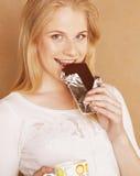 Muchacha rubia linda joven que come el chocolate y que bebe ascendente cercano del café Imágenes de archivo libres de regalías